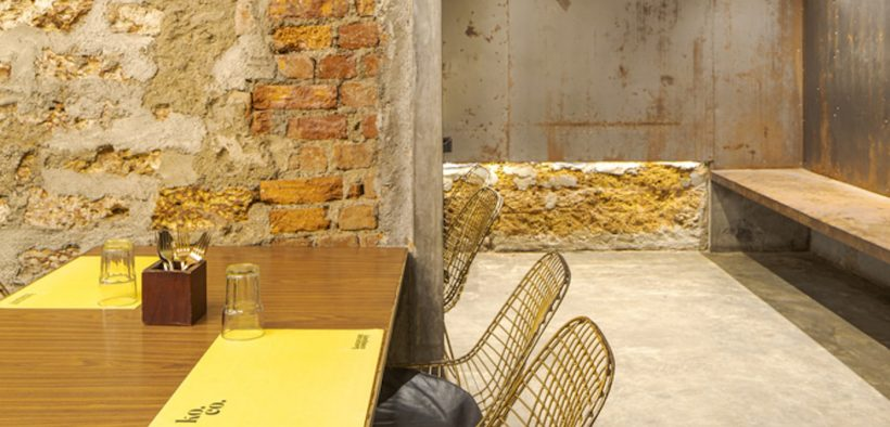 Dining table next to old brick wall and metal sheet