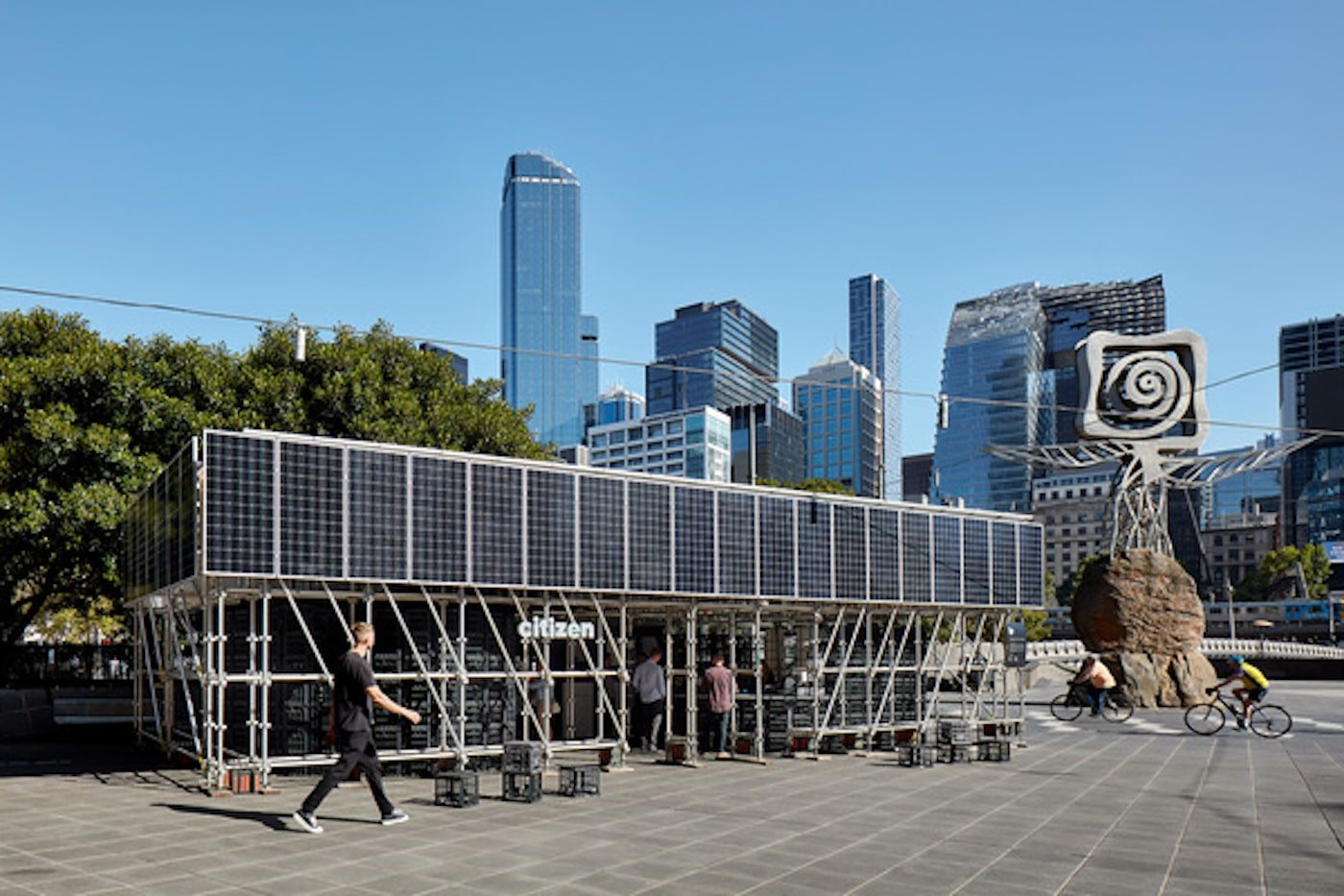 Person walking past pavilion with solar panels on facade