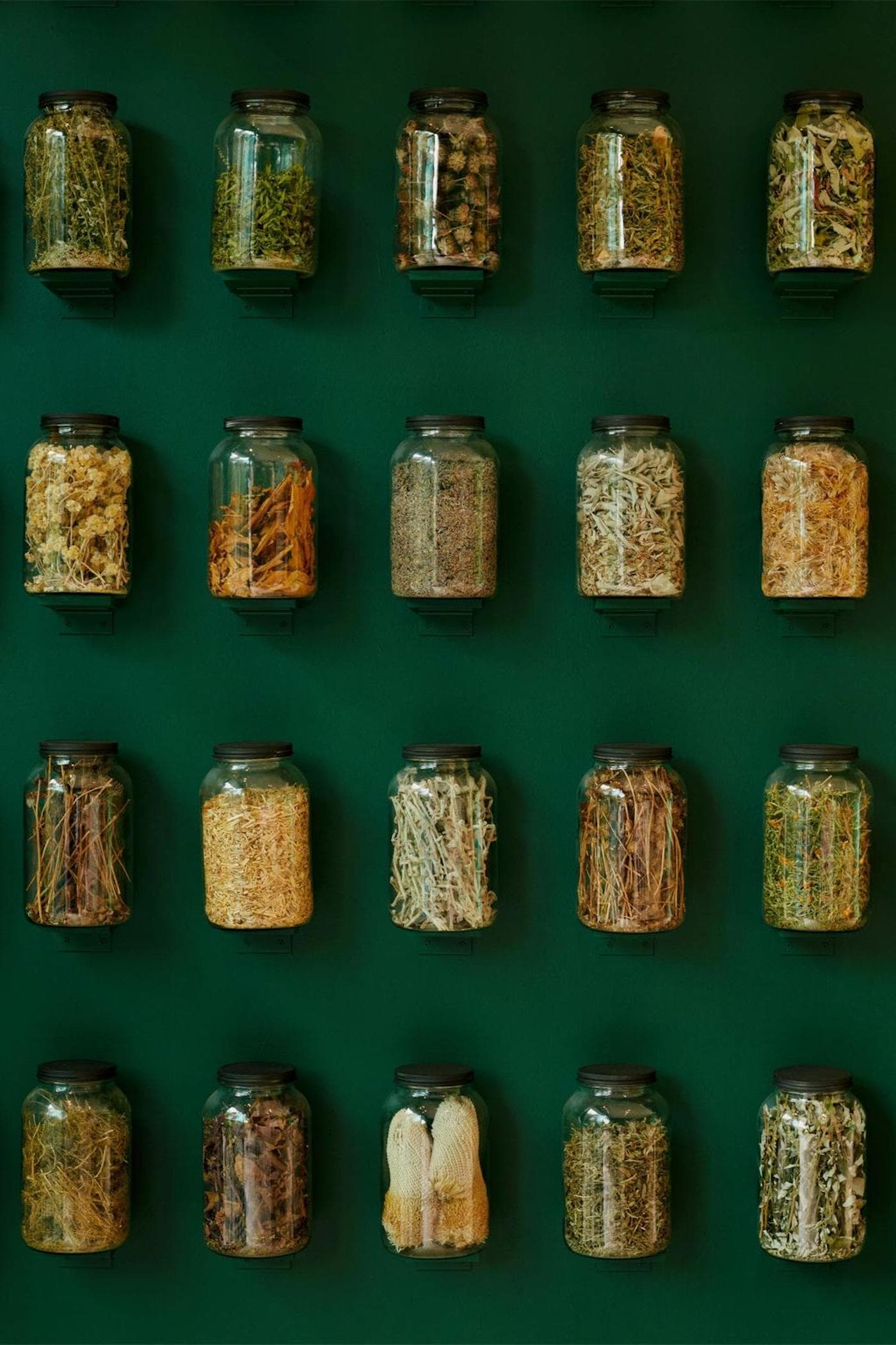 Close up view of ingredients in glass bottles on green wall