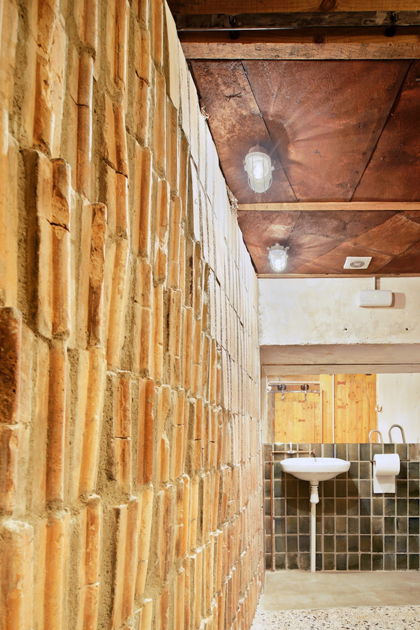 Recycled bricks and timber ceiling in bathroom