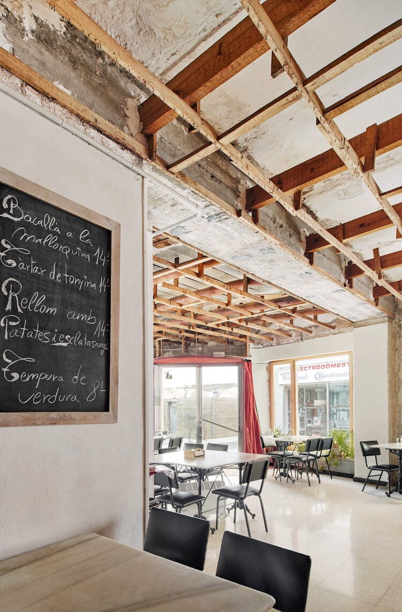 Exposed timber ceiling and concrete floors in cafe