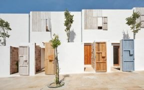 Colourful recycled timber front doors with white lime concrete facade
