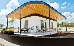 External view of 3D printed house with timber lined veranda roof