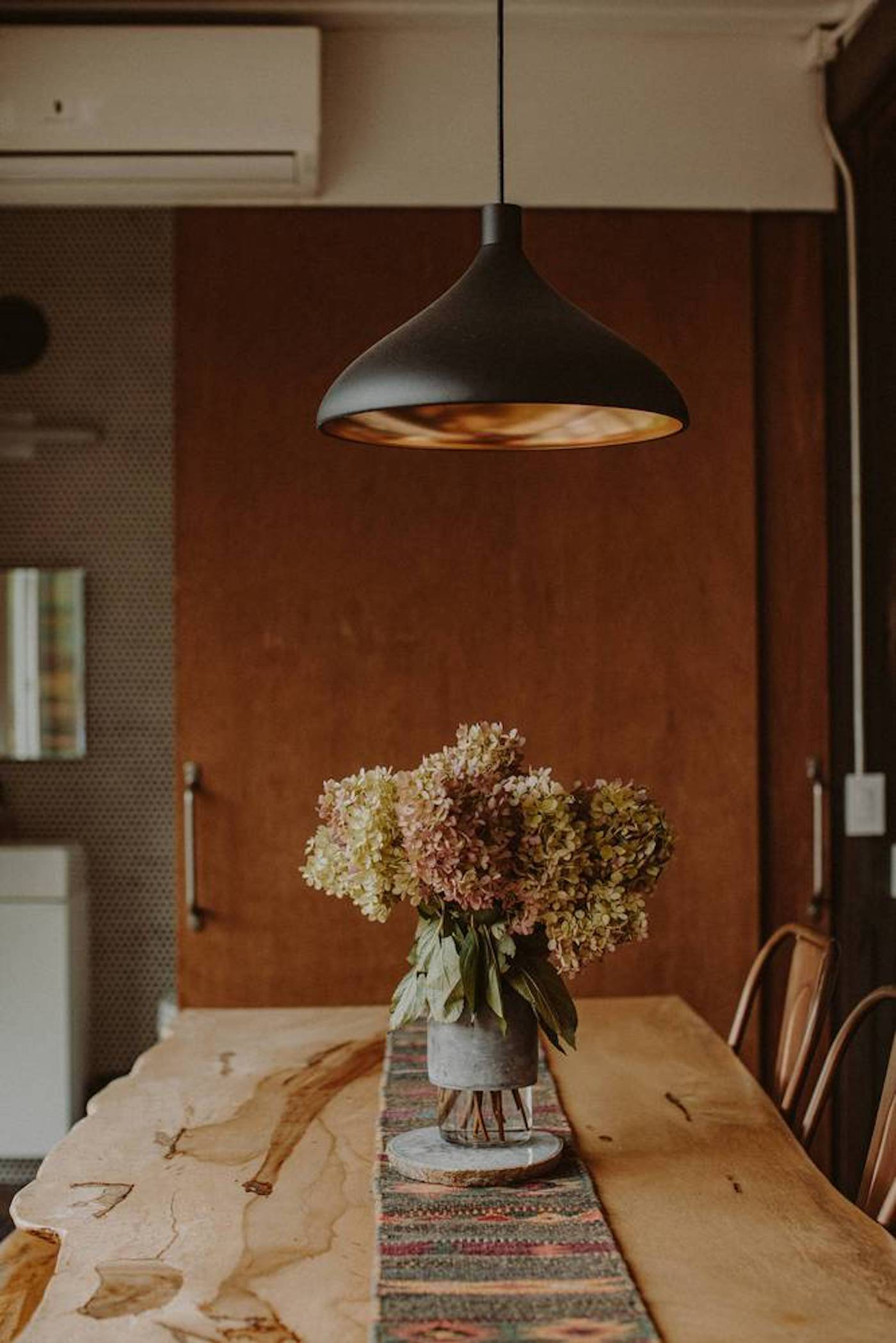 Timber dining table with black pendant light hanging above