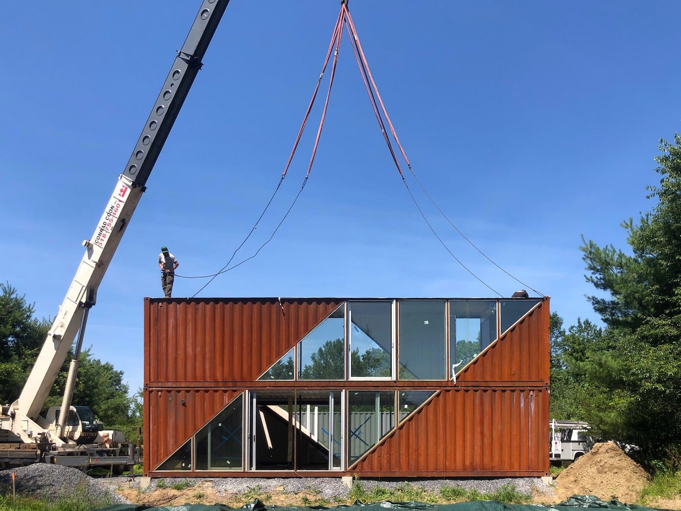 Crane lowering shipping container home into place
