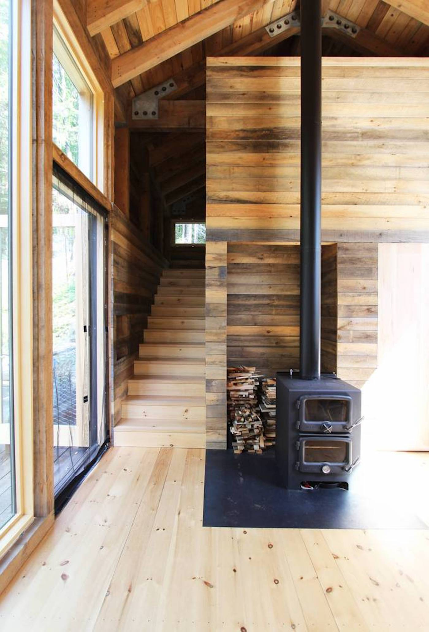 Fireplace inside timber clad off-grid cabin