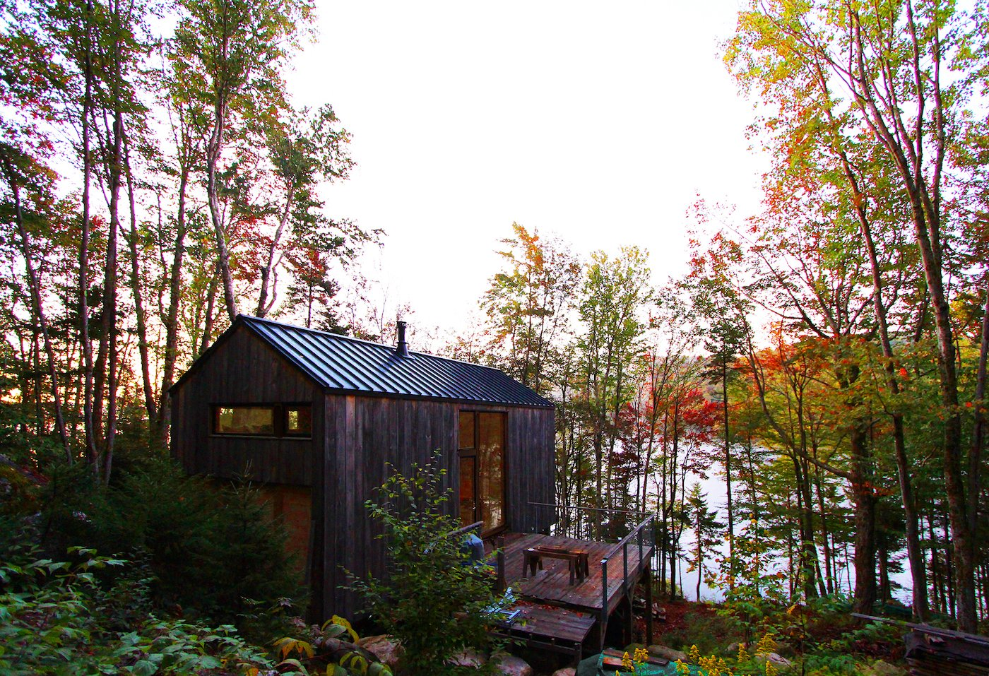 View of lake and woods surrounding off-grid timber cabin