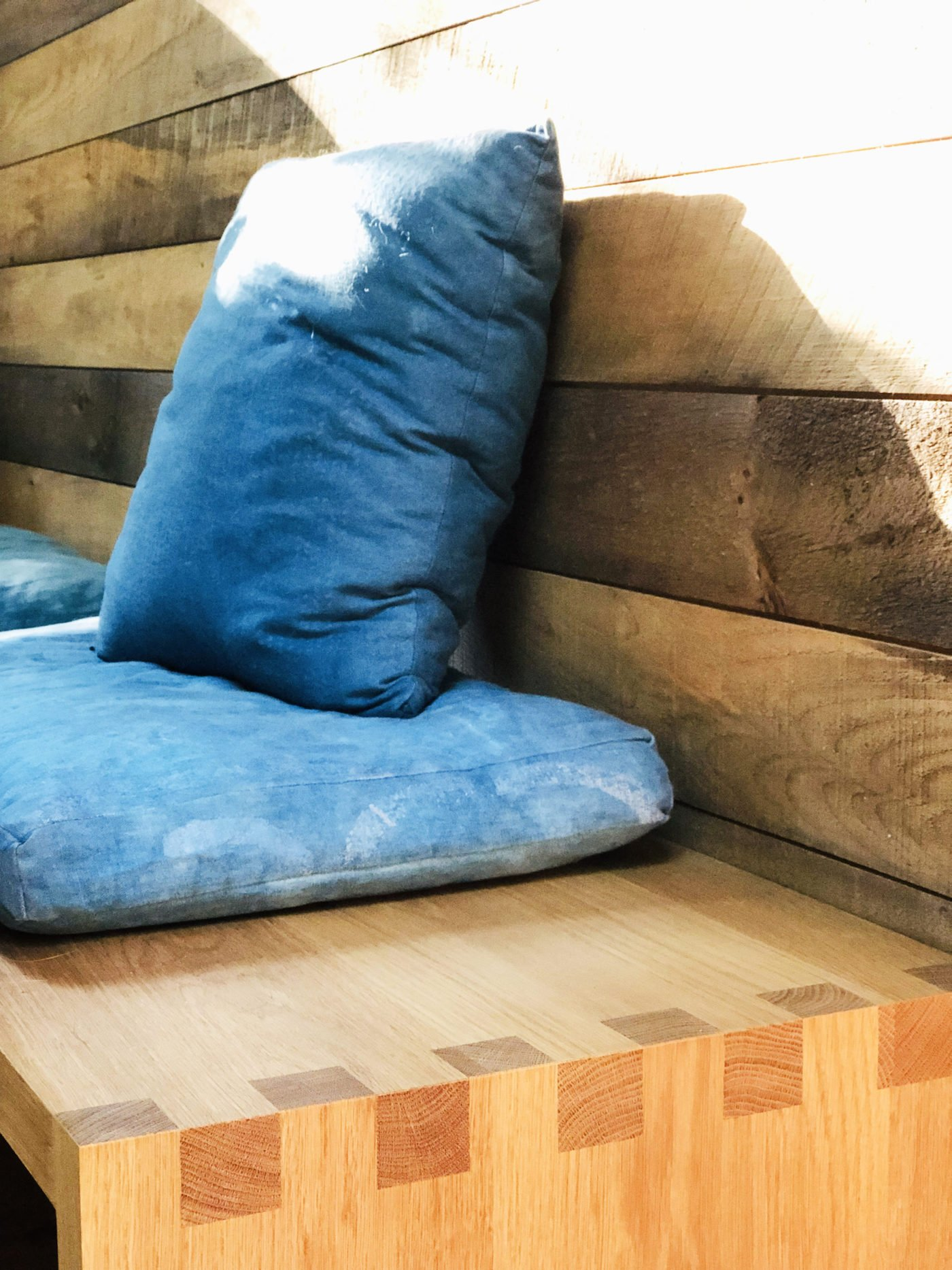 Detail of timber bench seat with blue cushions
