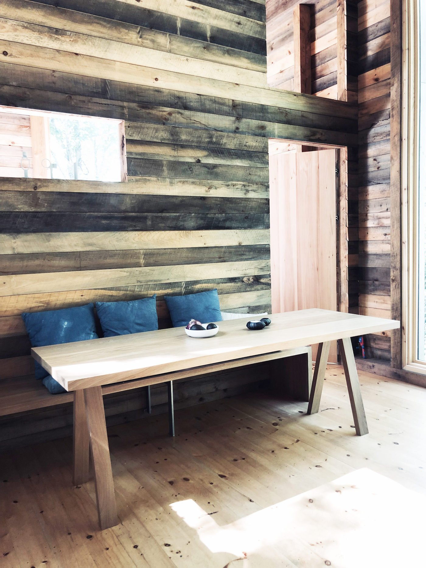 Timber dining table in cabin with timber walls and timber floor