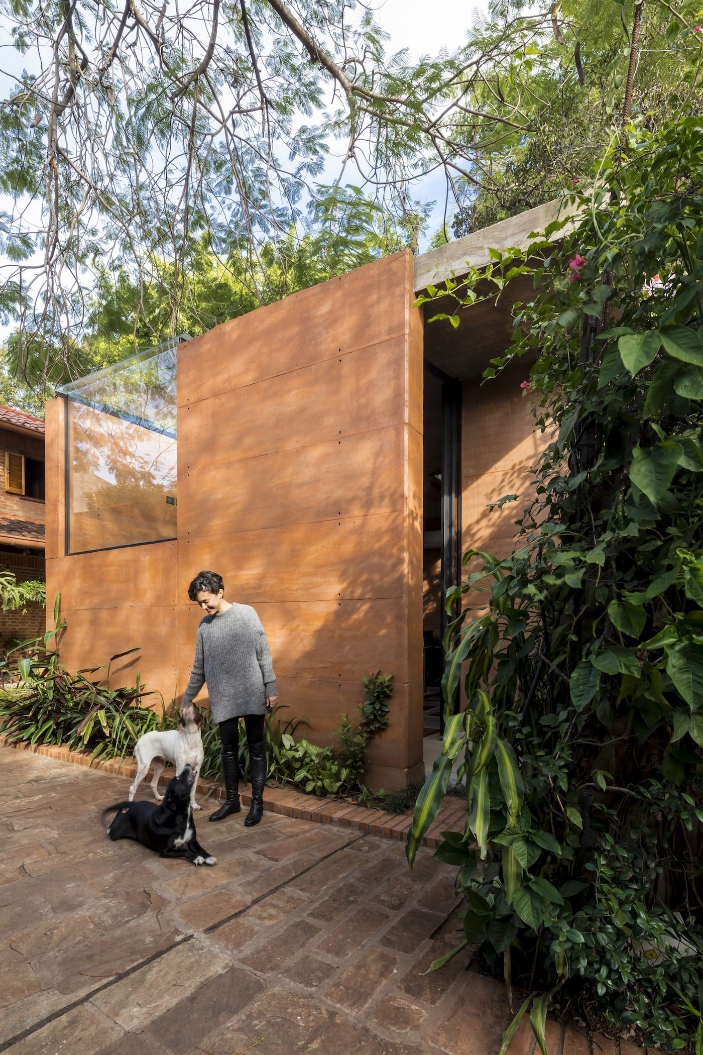 Woman and dogs in front of rammed earth office building