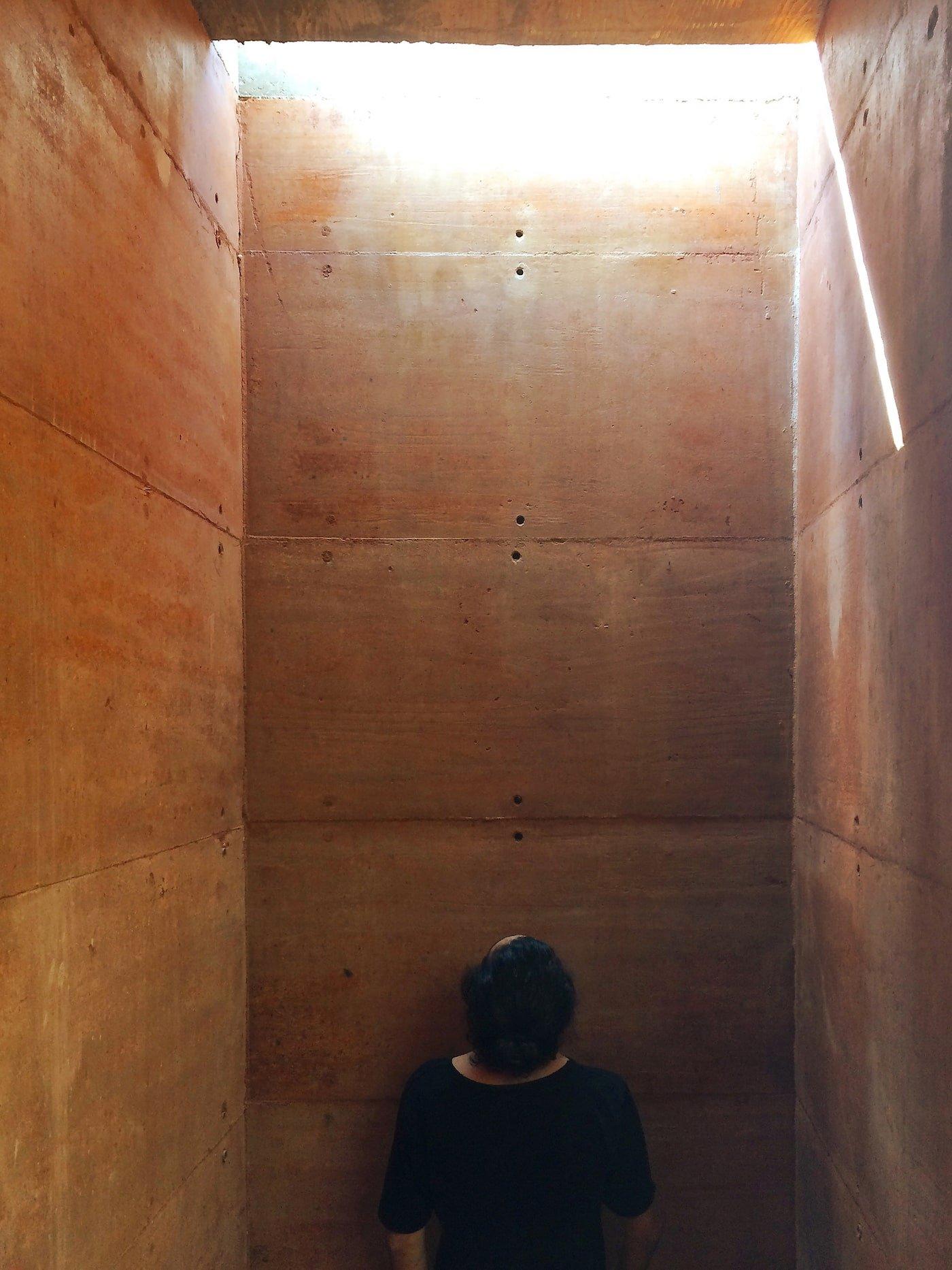 Man standing in light well inside rammed earth building