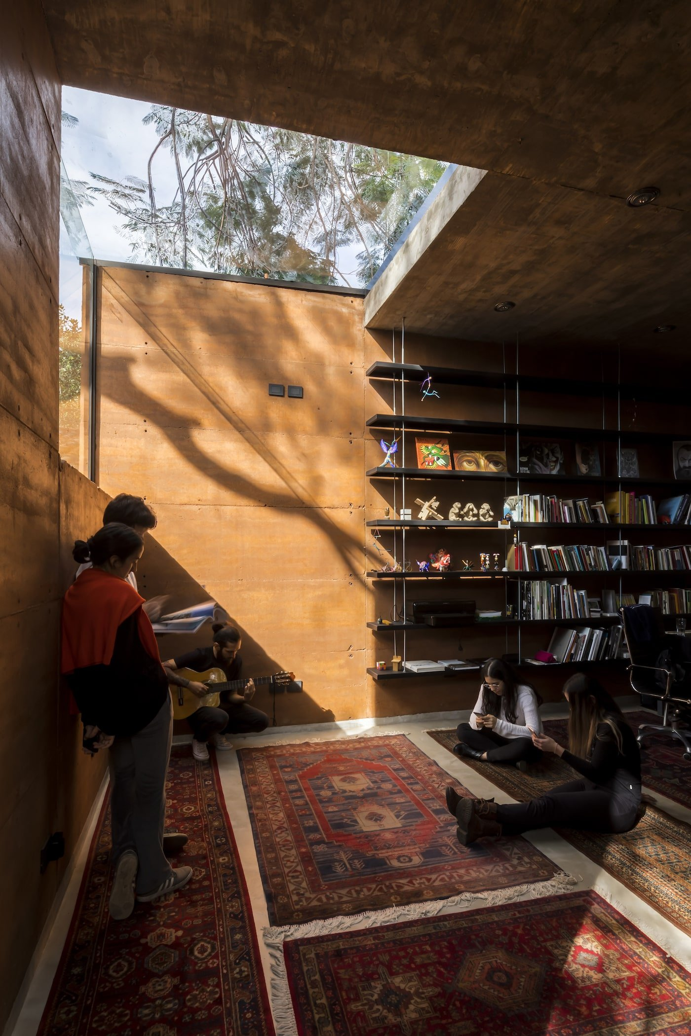 Team collaboration next to bookcase in rammed earth office
