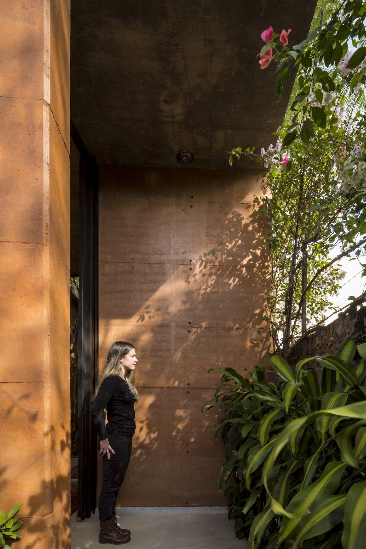 Woman standing near plant wall in rammed earth building