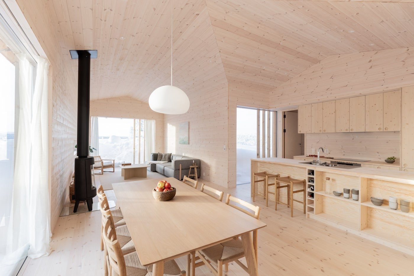 Timber dining table next to all timber kitchen in Kvitfjell Cabin