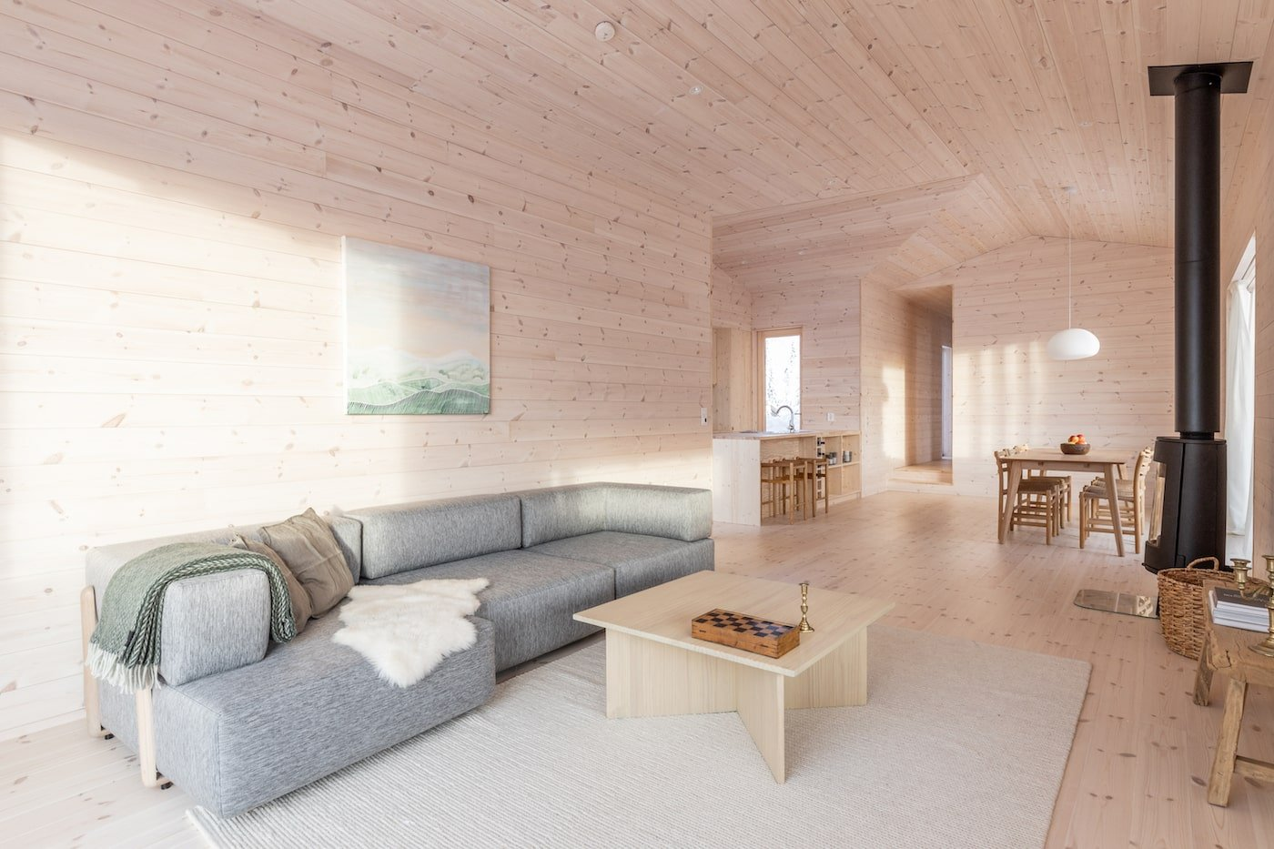 Grey lounge in timber lined lounge room of Kvitfjell Cabin