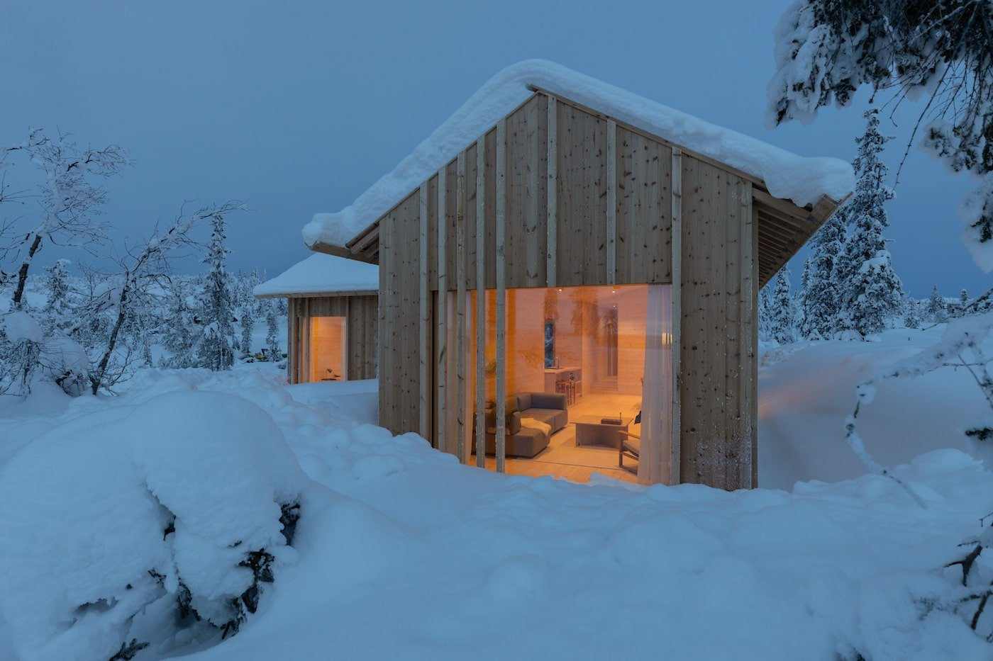 Exterior night time view looking into lounge room of Kvitfjell Cabin