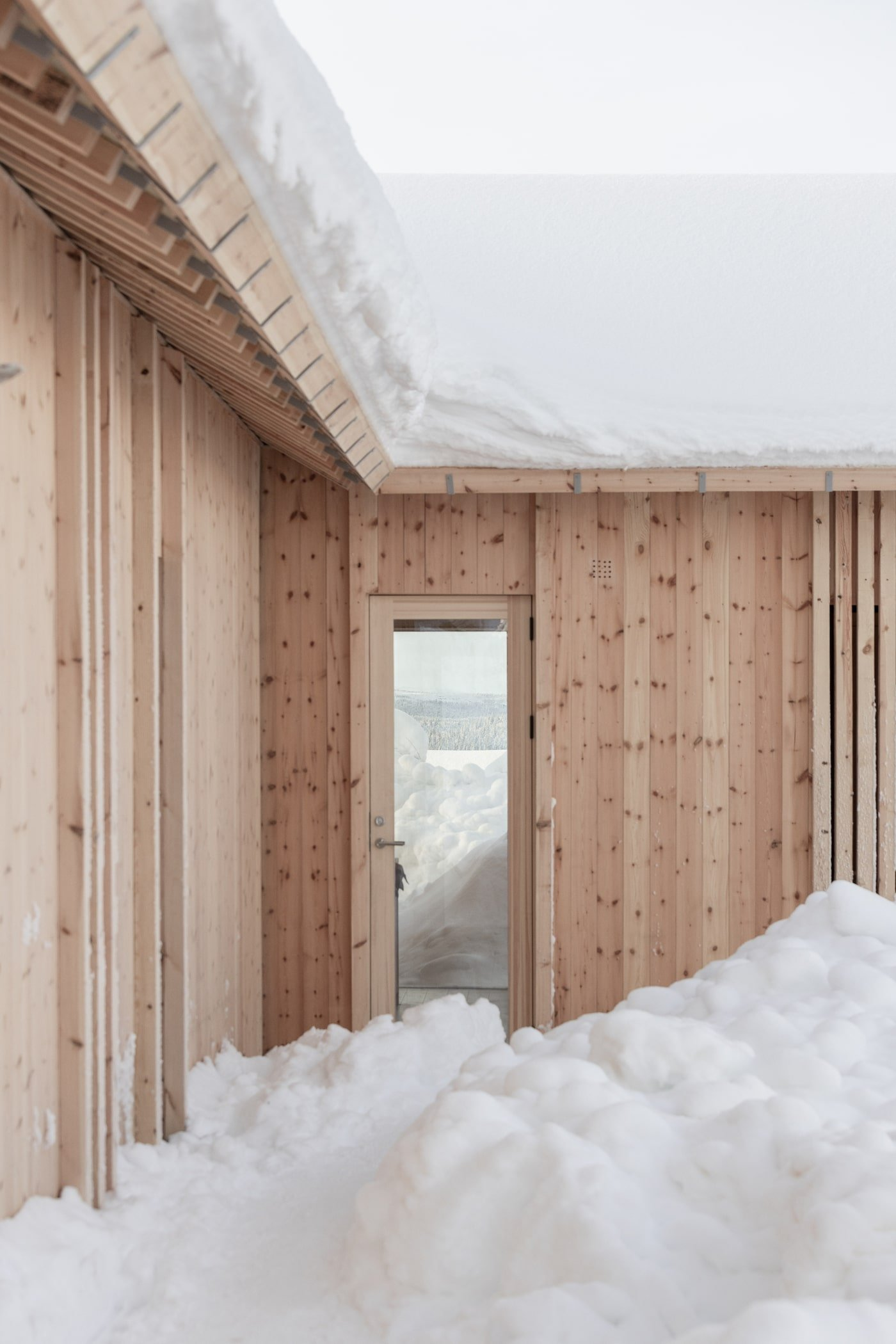Snow piled up in front of door of all timber Kvitfjell Cabin