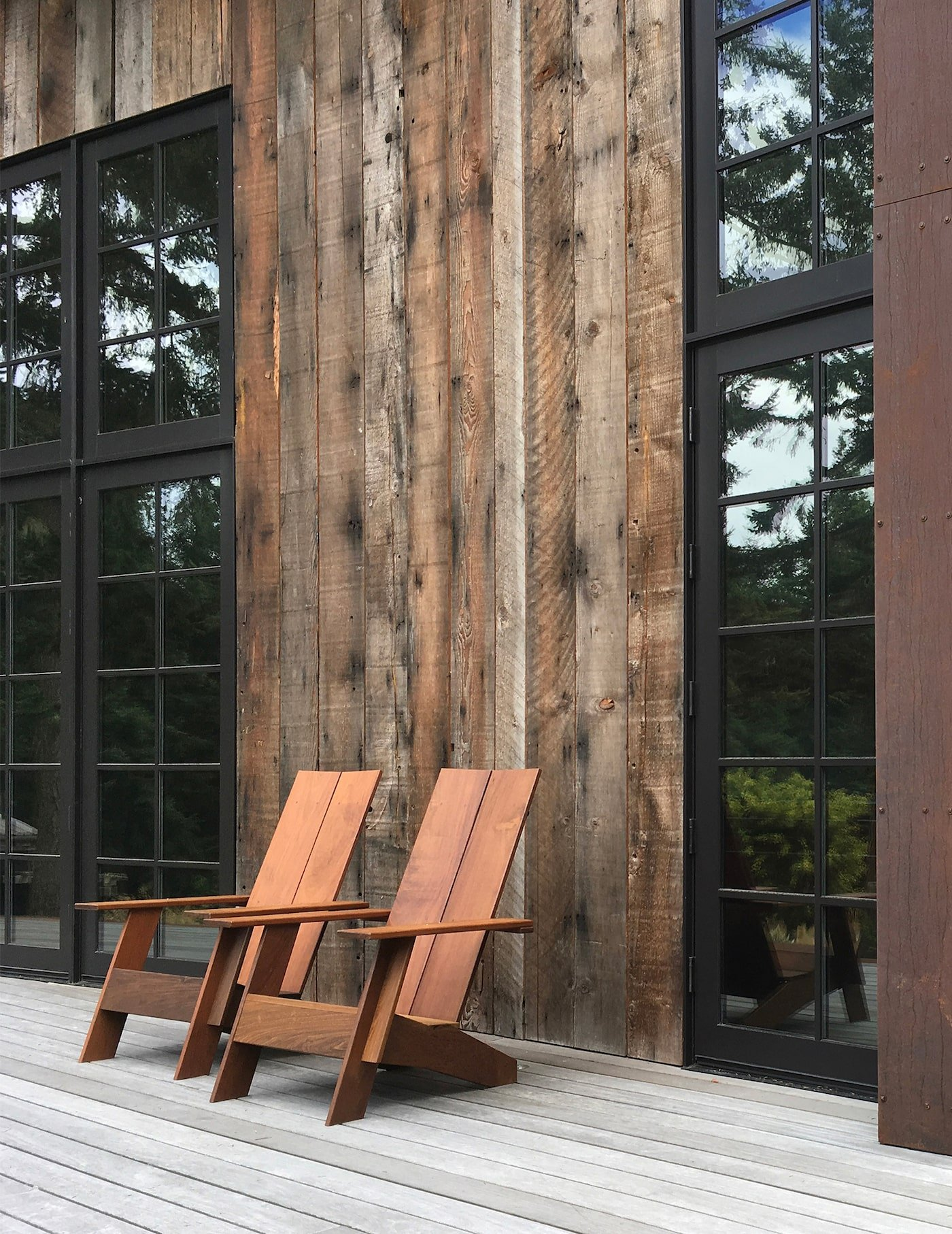 Close up of timber chairs in front of timber clad eco retreat