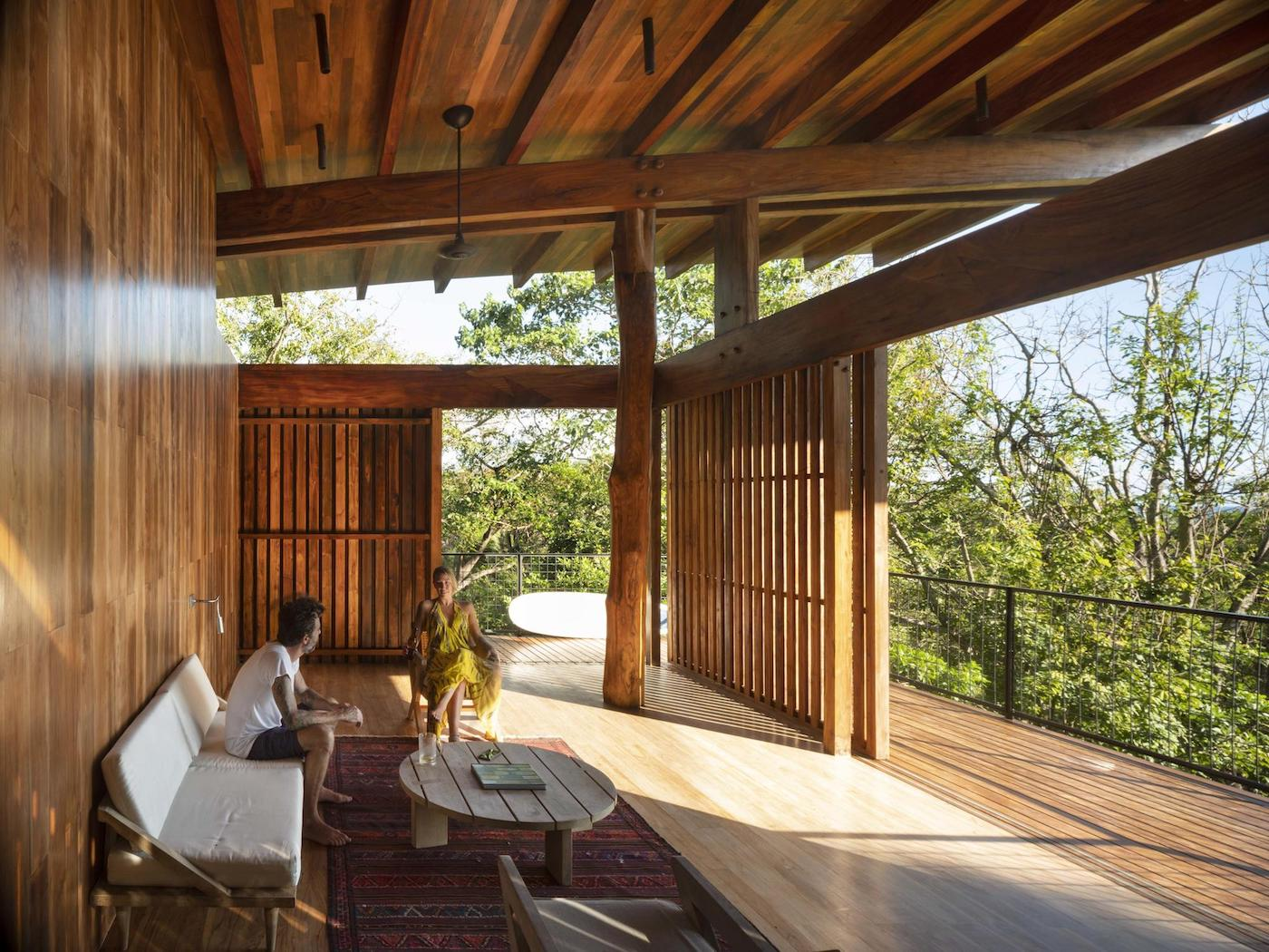 Man sitting on lounge in open-air timber home