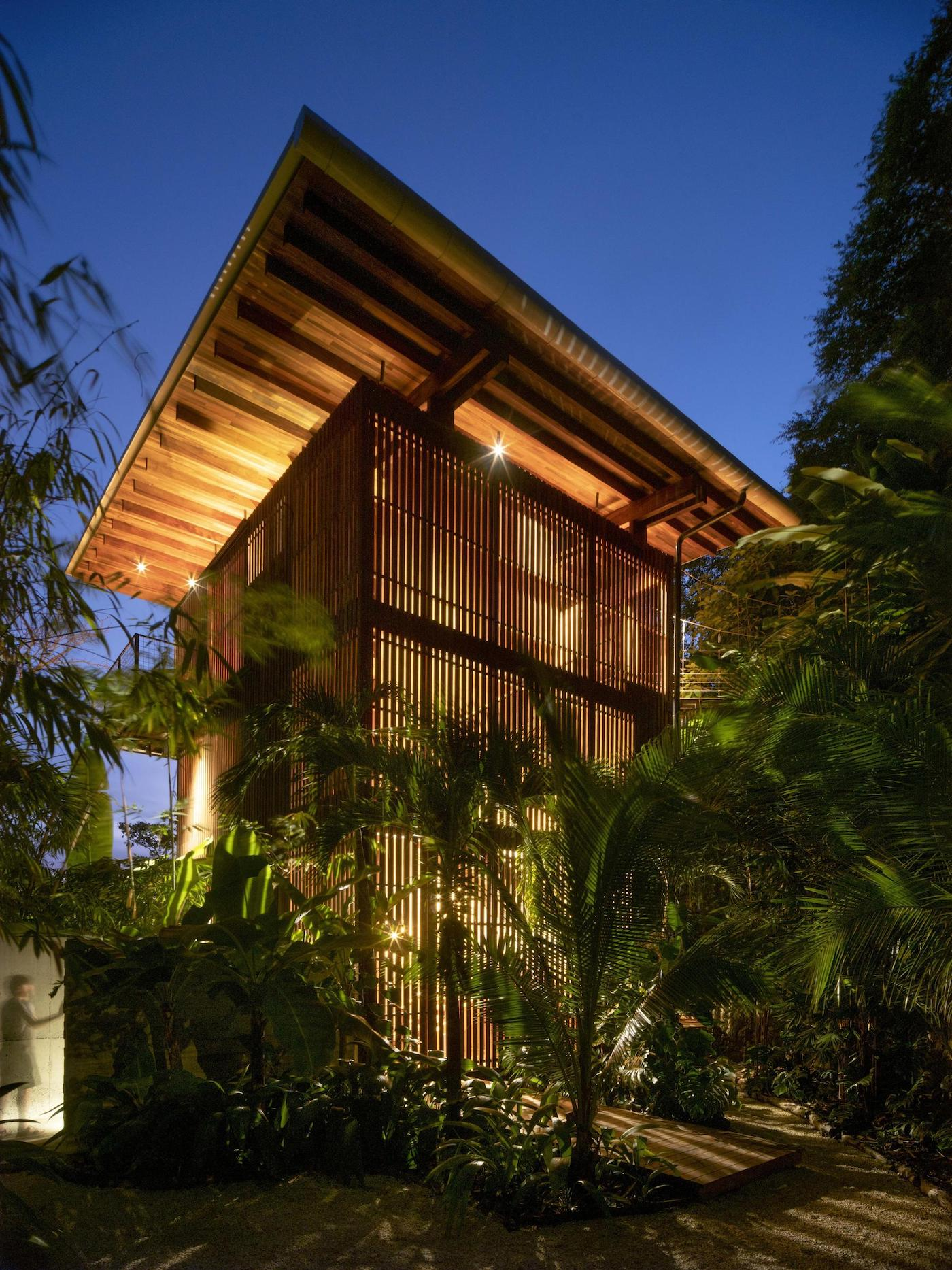 Night time external view of open-air timber home