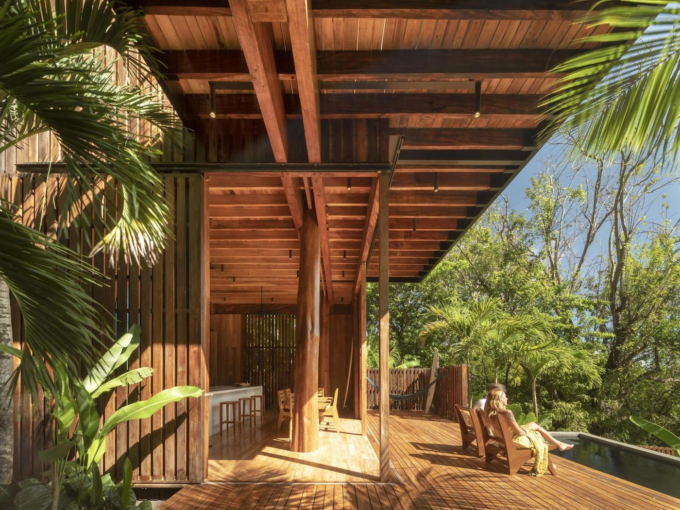 Couple sitting on timber deck of timber home overlooking pool