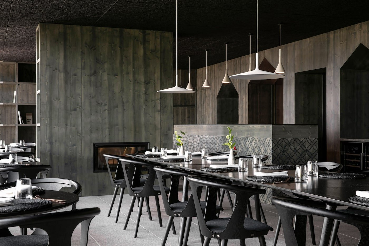 Stone bar in blackened timber lined restaurant