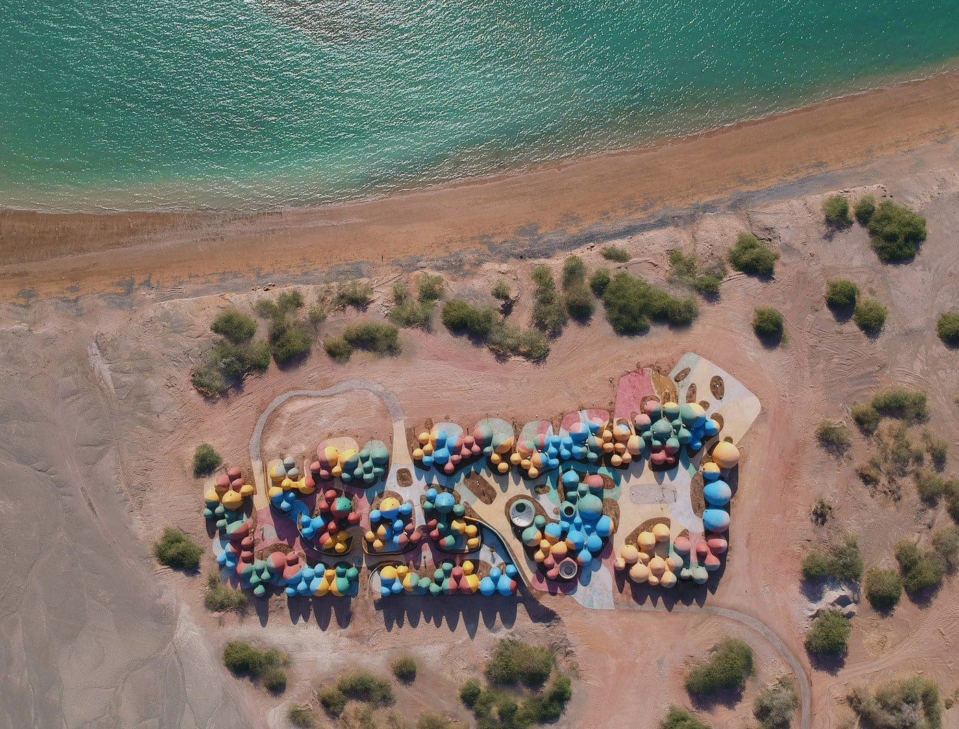 Aerial view of colourful rammed earth community Presence in Hormuz