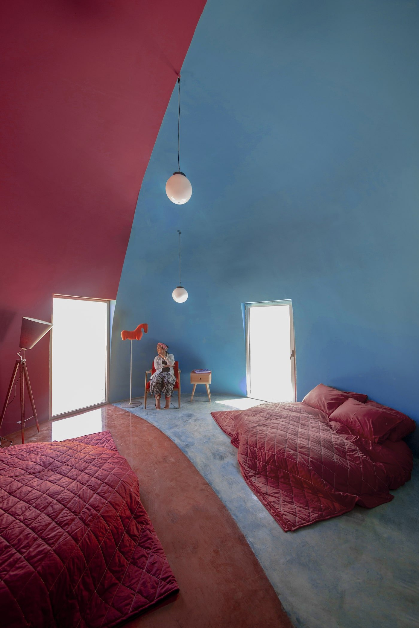Pink and blue bedroom in rammed earth dome