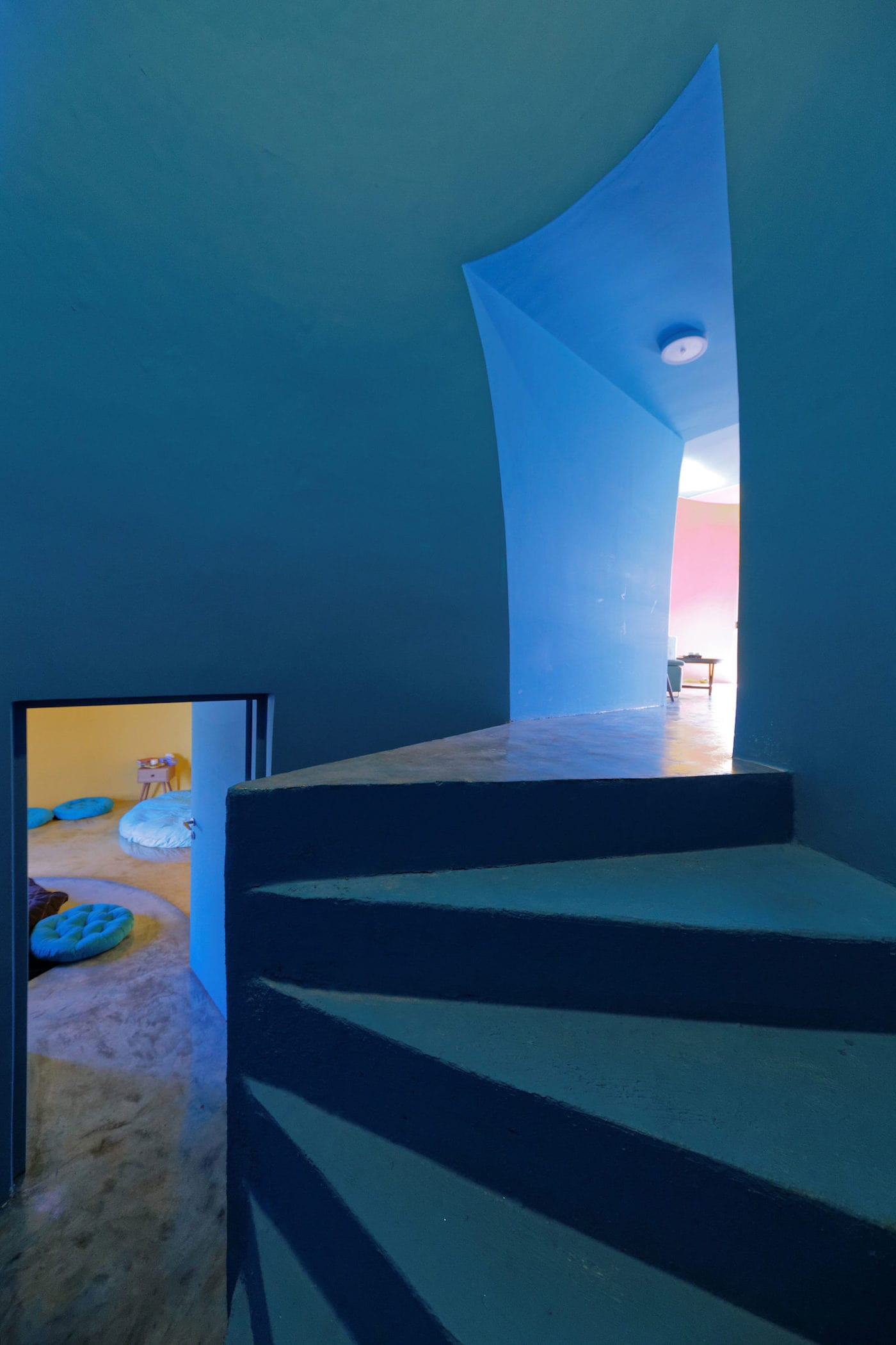 Curved blue staircase in rammed earth dome