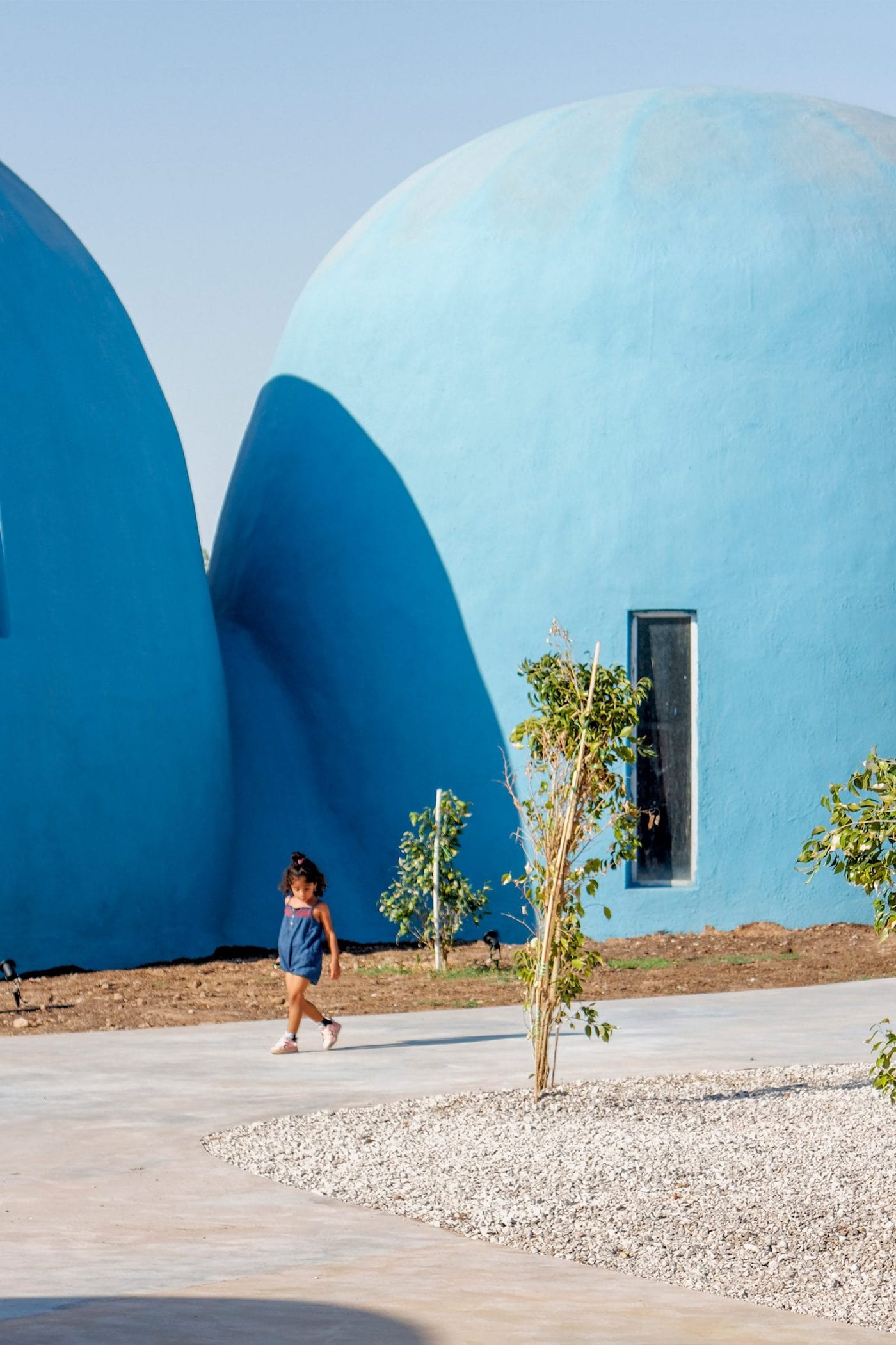 Girl walking in front of blue rammed earth dome