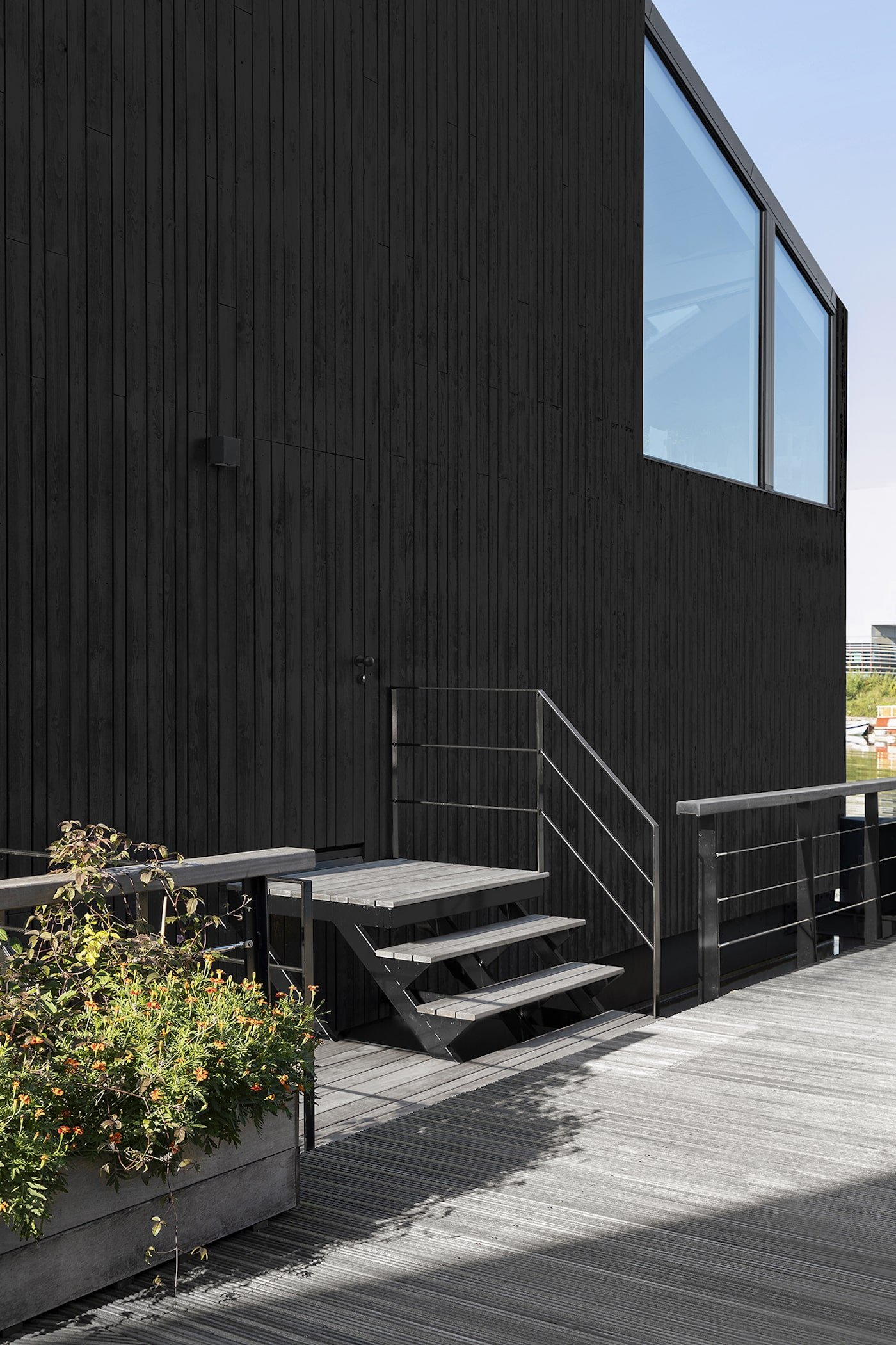 Entry door to black timber clad floating home