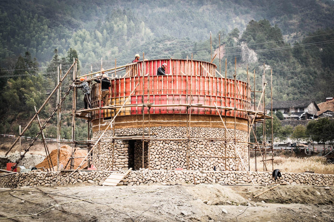 Construction of circular rammed earth and stone building