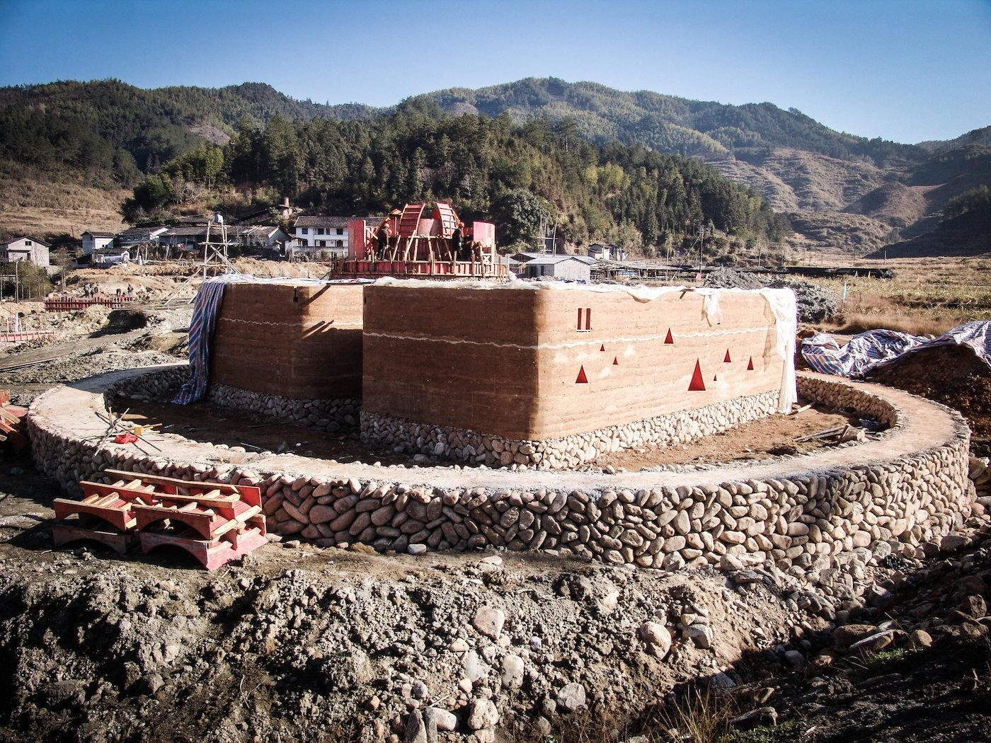Rammed earth and stone building in construction