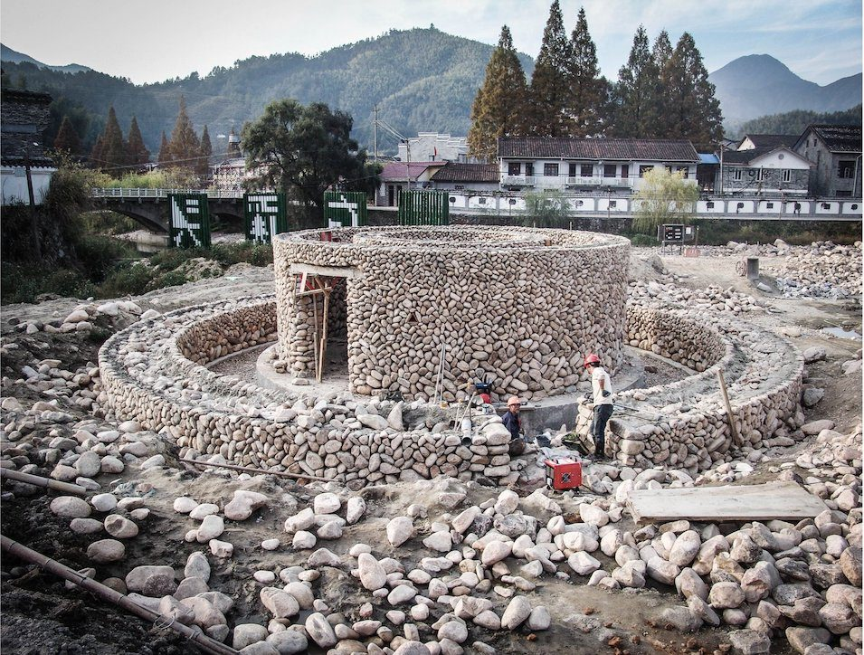 Construction of rammed earth and stone levels of bamboo building