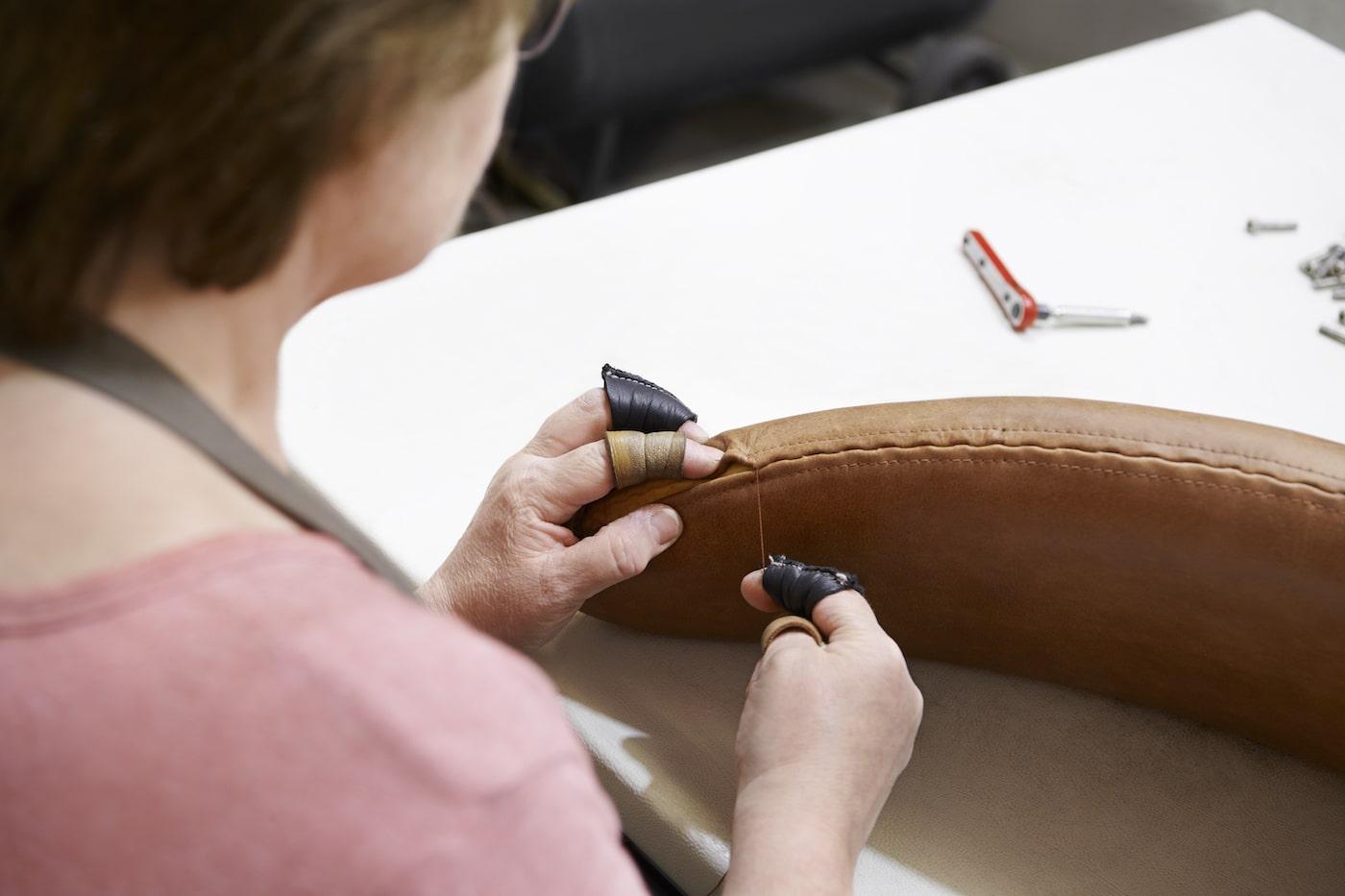 Woman sewing new leather onto Erik Jorgensen Corona chair