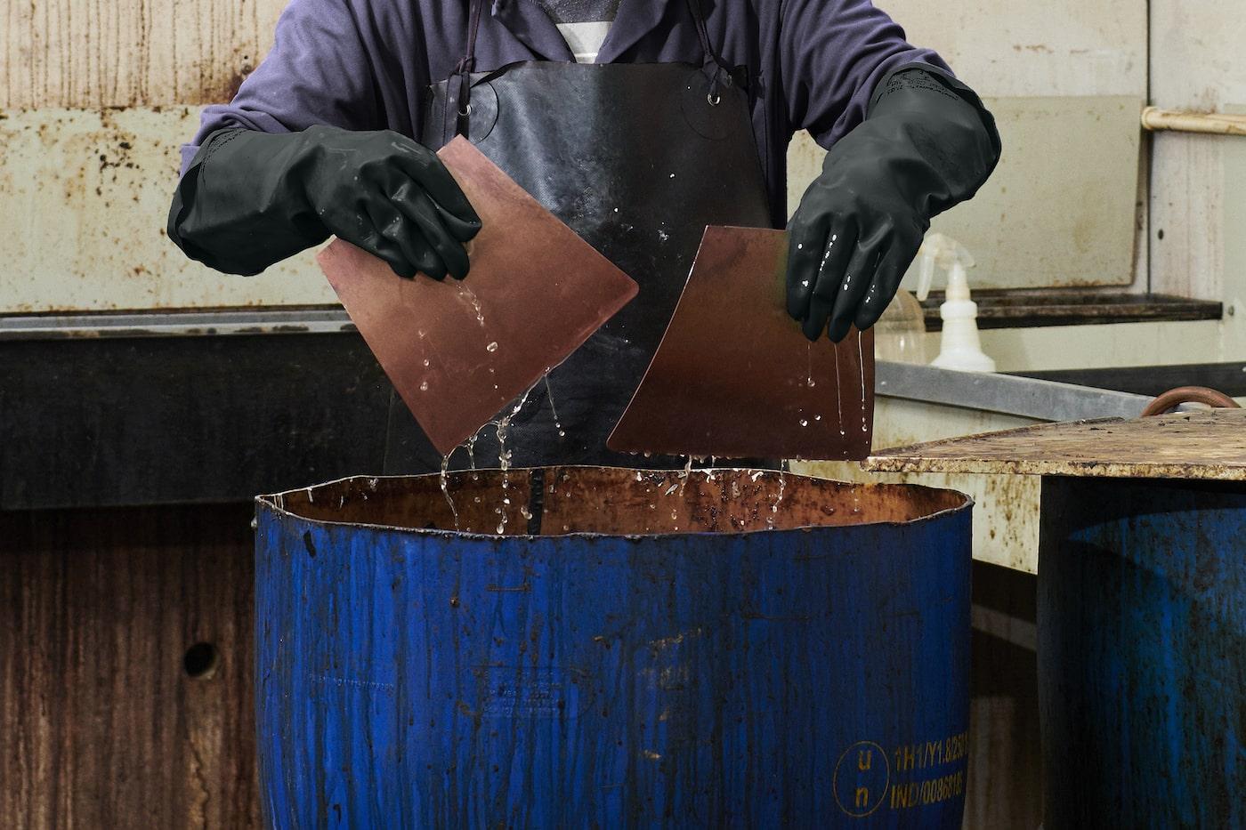 Man cleaning copper leaves on a Louis Poulsen Artichoke pendant