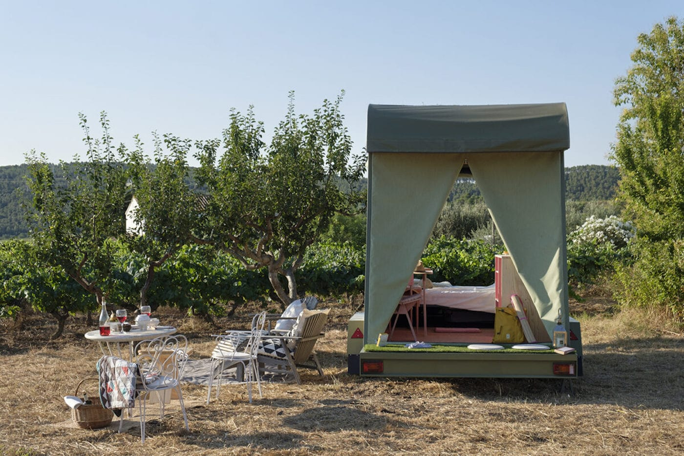 Campervan set up in vineyards with outdoor tables and chairs