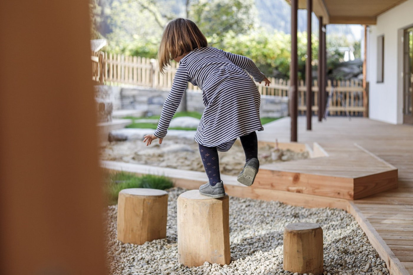 Girl layout outside on tree stumps in playground of Moar Gut childcare centre