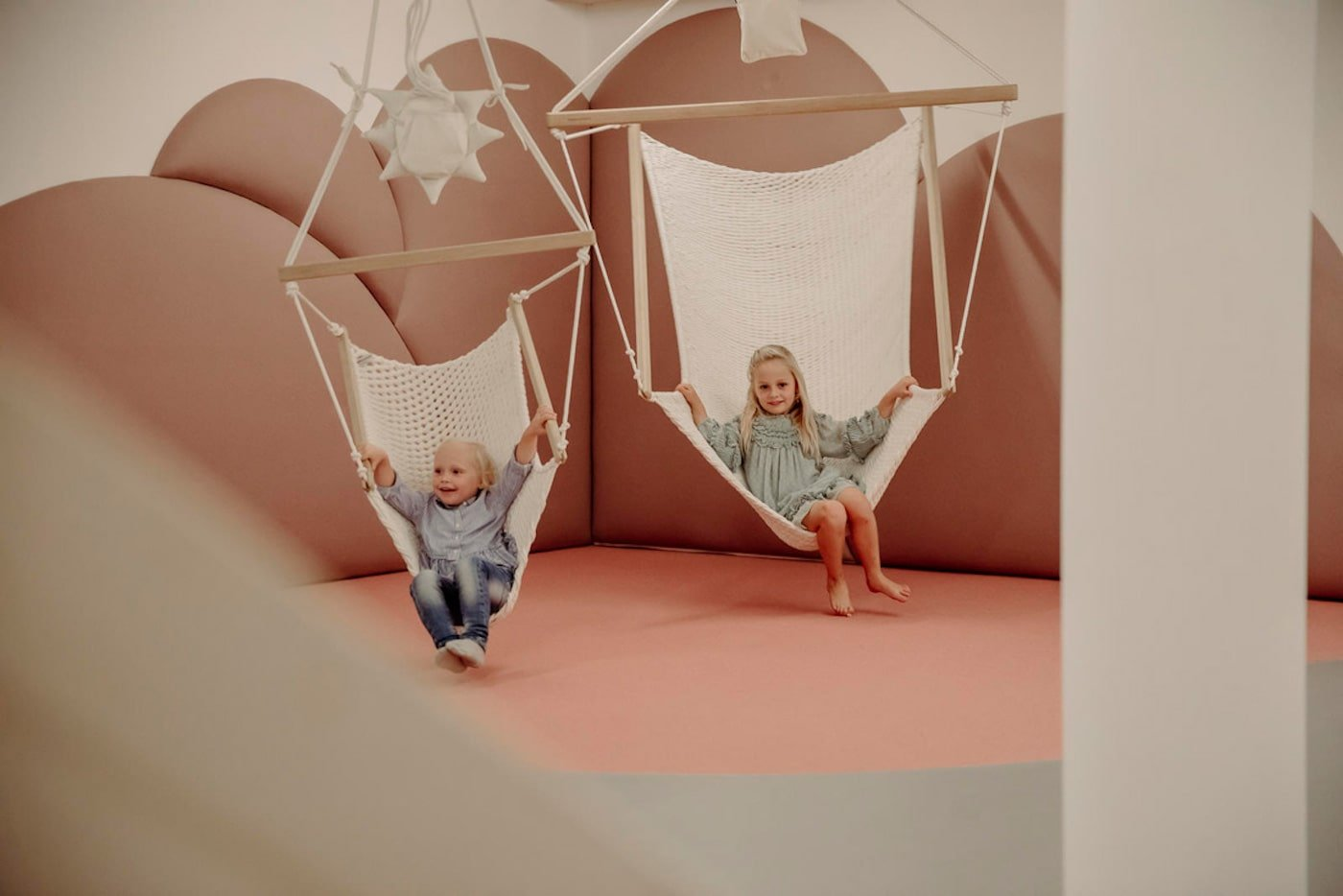 Kids sitting in chair swings in childcare centre