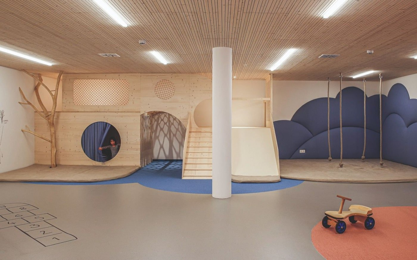 Playroom in childcare centre with blue clouds on wall and timber furniture