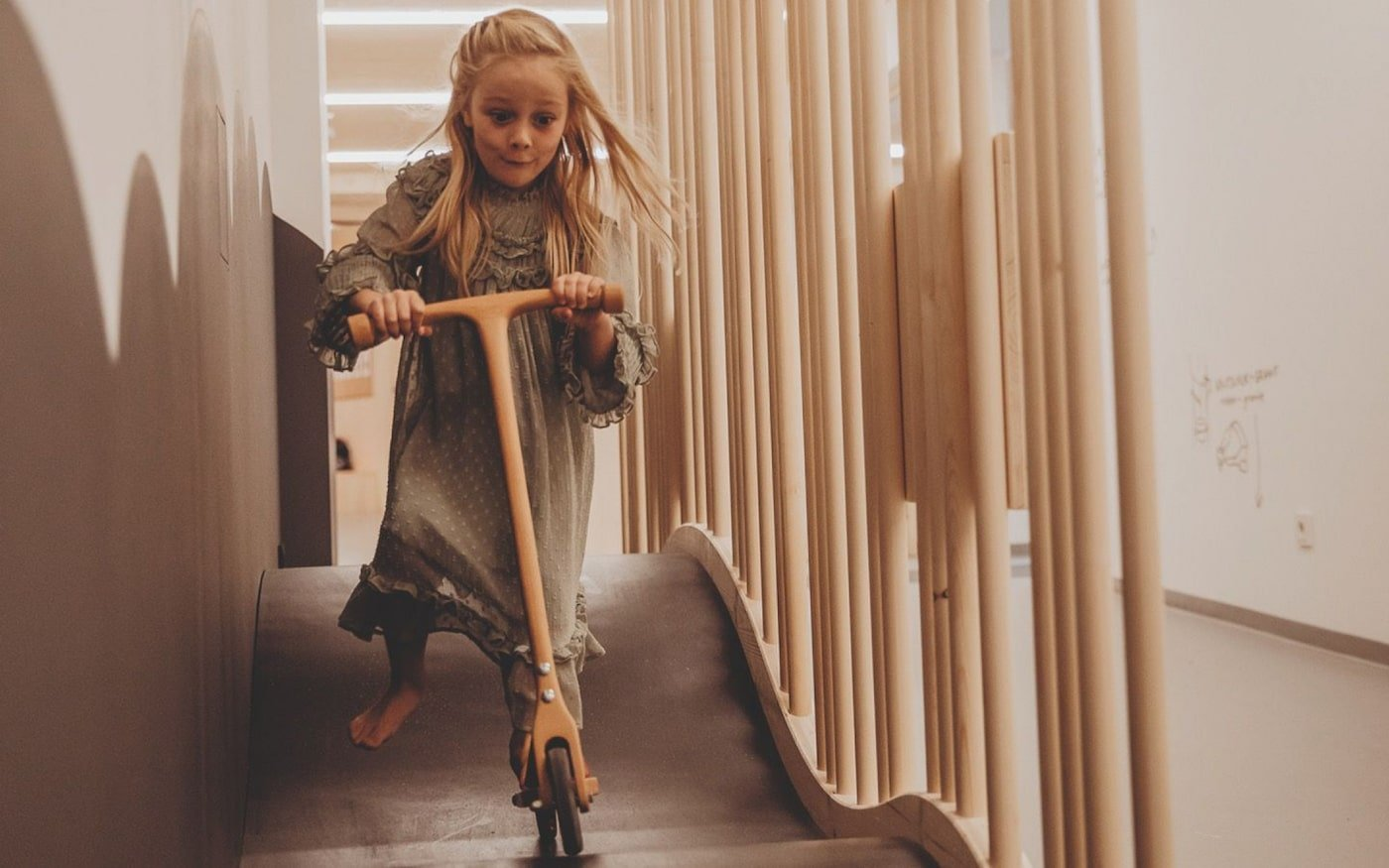Girl riding a timber scooter on a wavy ramp inside all natural childcare centre