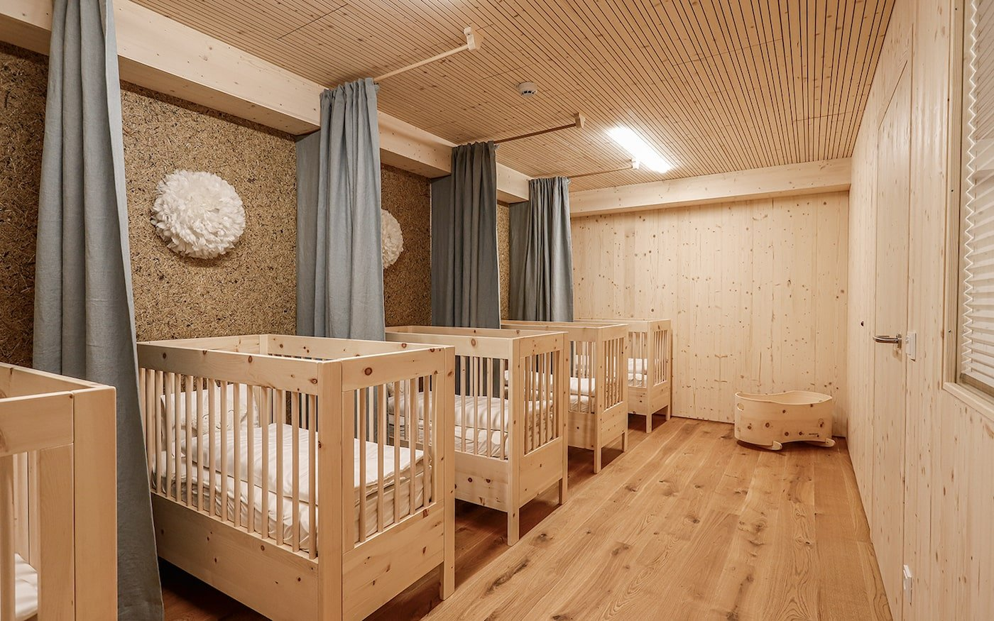 Cot room with timber furniture in sustainable childcare centre
