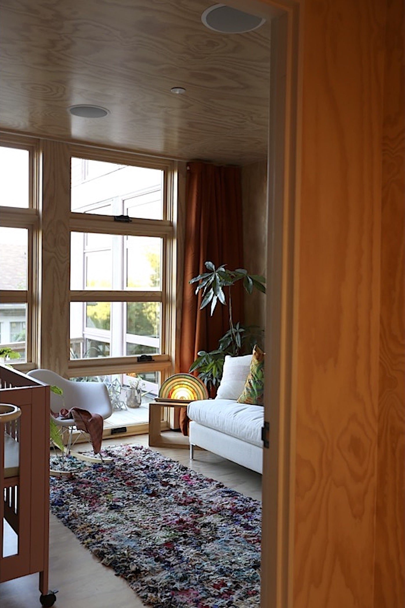 View into loungeroom with timber walls and timber windows