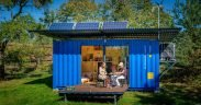 Blue shipping container with solar panels and wind turbine
