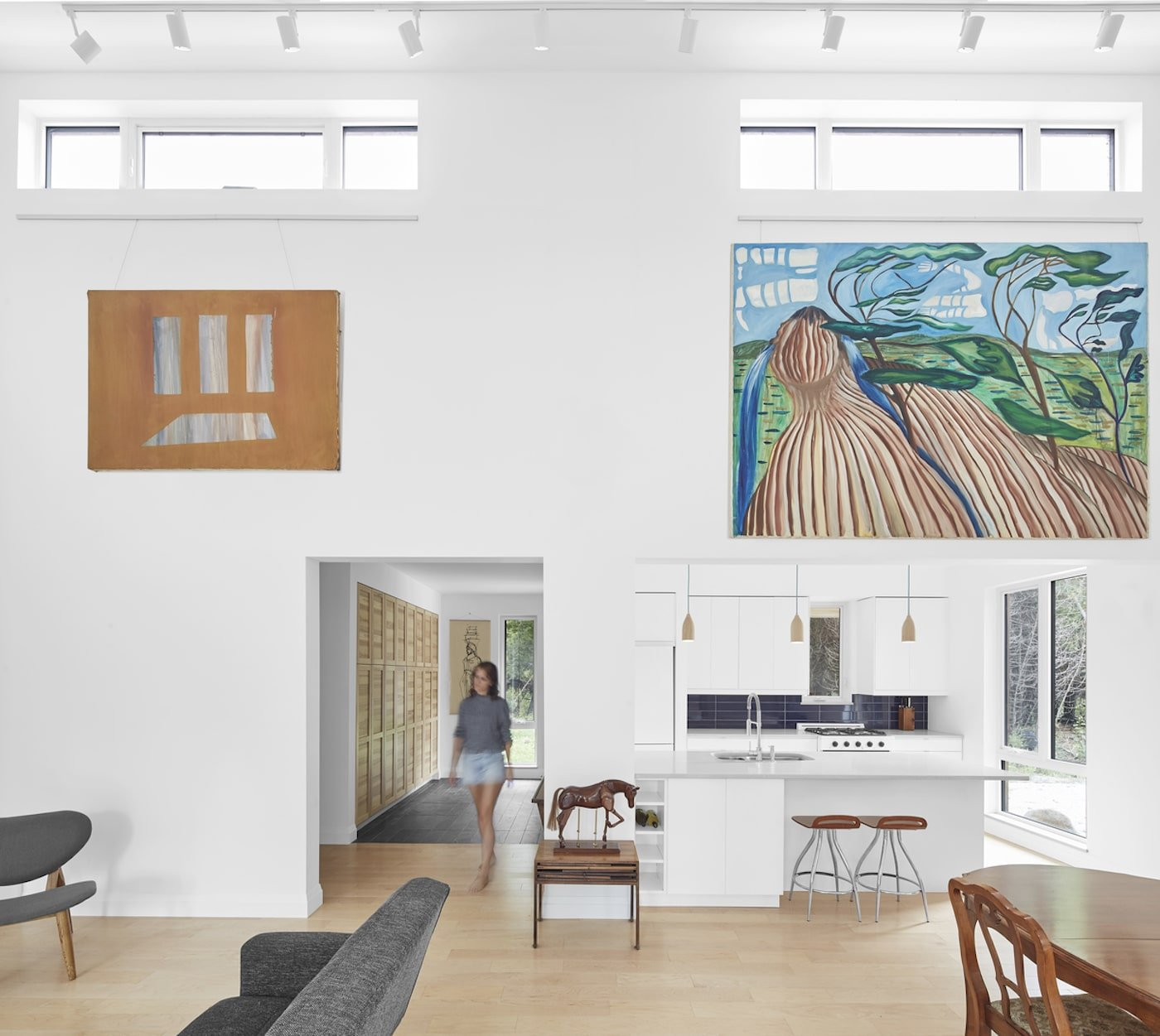 Woman walking through lounge room with art on walls of off grid house