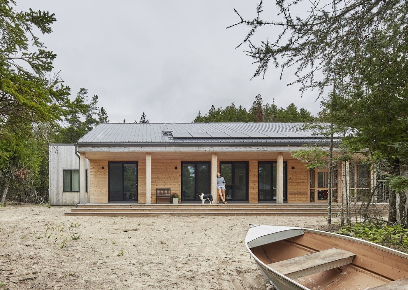 Timber rowboat in front of off-grid timber house