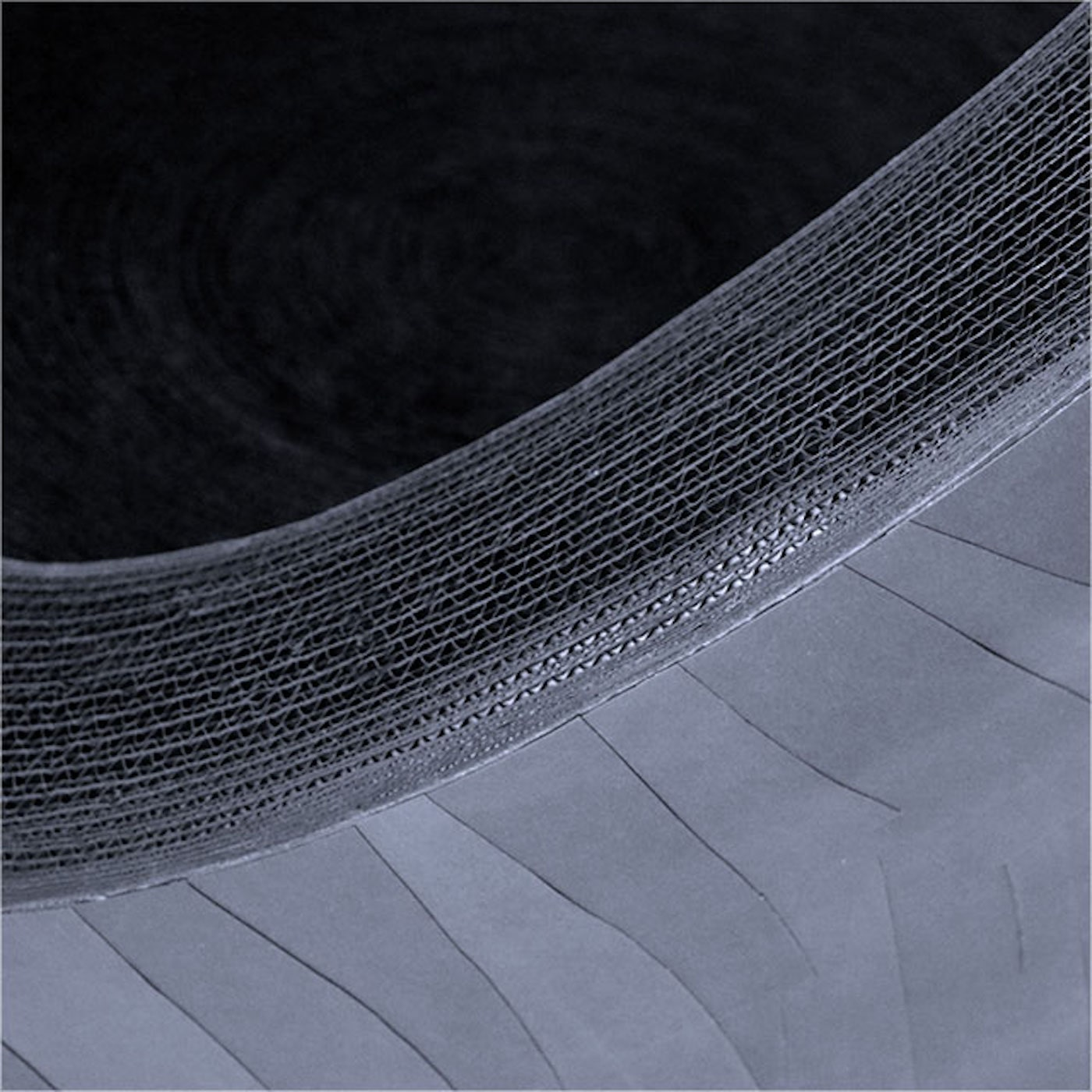 Detail view of curved black cardboard chair