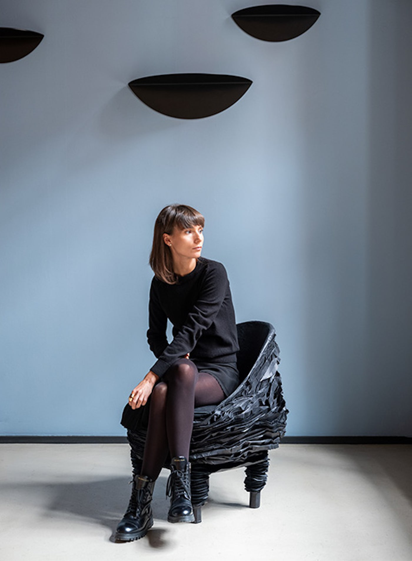 Woman sitting on black chair made from recycled cardboard