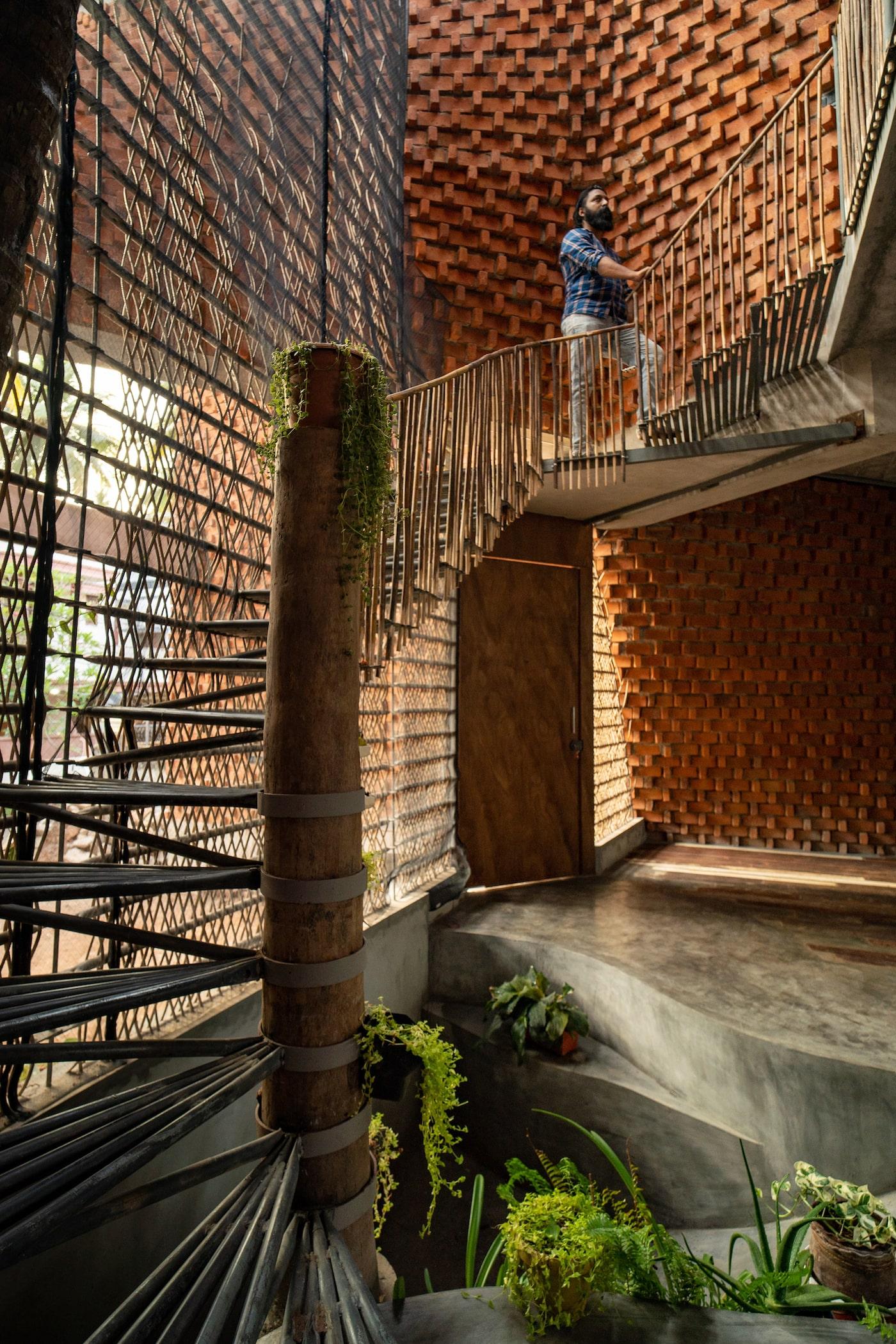 Man walking up metal stairs in brick home