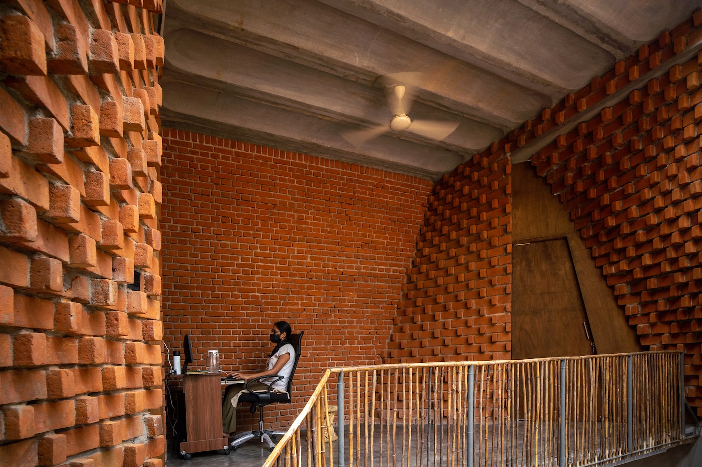 Woman sitting at desk on mezzanine level in Pirouette House made from bricks